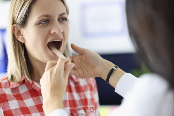 Doctor-Looking-At-Throat-Of-Wo-397796054